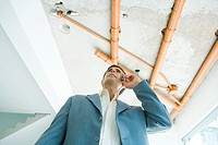 Man in suit using cell phone, bare pipes overhead, low angle view