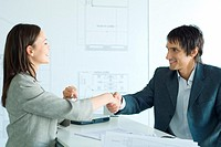Woman and man shaking hands across table in architect firm