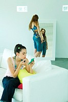 Teenage girl on couch putting on lipstick, looking at self in hand mirror, friend in background