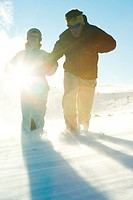 Father and daughter running in snow, dressed in winter clothing, full length