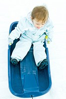 Toddler sitting on sled, dressed in winter clothing, high angle view