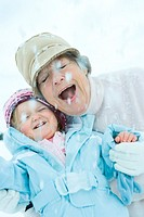 Senior woman and granddaughter cheek to cheek in snow, smiling, eyes, closed