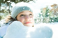 Teenage girl looking up at snow, smiling, portrait