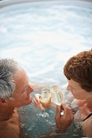 Couple in Hot Tub Toasting with Champagne