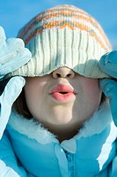 Girl pulling knit hat down over eyes, puckering, close-up