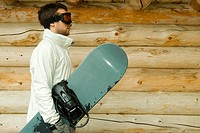 Young man holding snowboard, side view