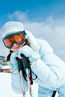 Teen girl leaning on ski poles, smiling at camera