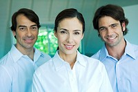 Businesswoman and two businessmen smiling at camera, head and shoulders, portrait