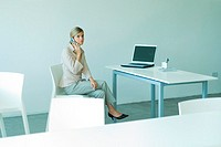 Young businesswoman seated in office, using cell phone, full length