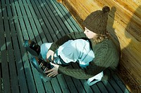 Teenage girl sitting on ground, putting on ski boot
