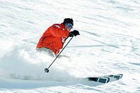 Mature skier on ski slope, smiling, blurred motion