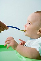 Baby being fed with spoon, side view