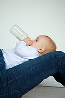 Baby reclining on lap, drinking milk from bottle, side view