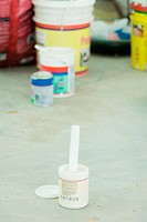 Paint can on the ground, open, painting materials in background