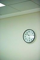 Clock hanging on wall under fluorescent light