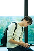 Male student in front of window, looking at cell phone