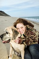 Teenage girl 16-18 crouching by dog on beach, smiling, portrait