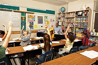 Schoolchildren 8-11 raising hands for teacher in classroom, rear view