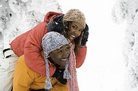 Young couple playing in snow, man carrying woman piggy back, laughing