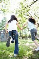 Two girls 8-9 running outdoors, rear view