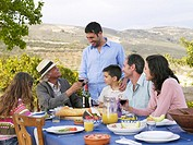 Multi-generational family having meal outdoors
