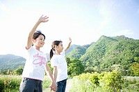 Two girls 8-9 waving in mountains
