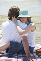 Young couple embracing during picnic at seashore