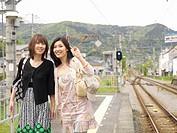 Two young women walking along train station platform, smiling