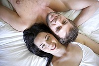 Young couple lying on bed, smiling, overhead view, portrait