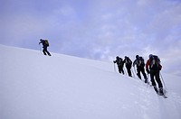 Group of people climbing in snow, one leading, low angle view, rear view