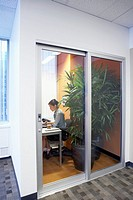 Female office worker sitting in office with large potted plant behind glass doors, side view