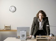 Young businesswoman leaning on desk in office, portrait