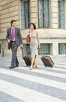 Business couple walking along zebra crossing with suitcases, smiling