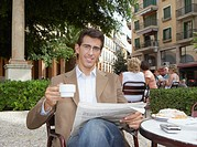 Businessman holding coffee cup, reading newspaper in cafe, smiling, portrait