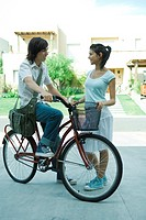 Teen boy on bike speaking to young female friend in residential neighborhood, full length