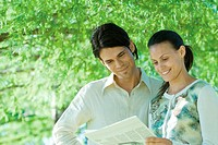 Couple standing outdoors reading newspaper