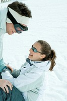 Brother and sister face to face in snow, brother bending over, sister sitting on the ground