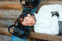 Young man lying on bench, resting head on snowboard, eyes closed