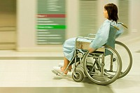 Female patient using wheelchair in hospital corridor, blurred motion