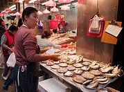 A fishmonger working hard in front of her stall in a local market in Hong Kong, China