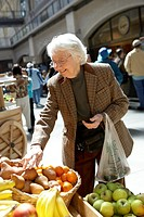 Older woman shopping at a fruit stand