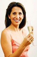 Mid adult woman holding wineglass, smiling, portrait