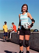 Young woman holding helmet, young men on background, smiling