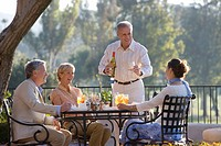 Two mature couples dining at outdoor restaurant table, man standing up, pouring glass of wine, smiling
