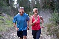 Active senior couple, in sportswear, jogging side by side along woodland path, smiling and laughing, front view, portrait