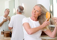 Senior couple getting ready in bathroom, man looking at reflection in mirror, focus on woman brushing long, straight hair with hairbrush in foreground...