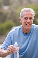 Active senior man, in blue t-shirt, holding plastic water bottle, smiling, front view, portrait