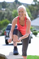 Active senior woman, in pink sports vest and leggings, tying trainer shoelace on driveway wall, smiling, front view, portrait