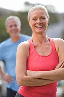 Active senior couple, in sportswear, standing on driveway, focus on woman in pink sports vest in foreground, arms folded, smiling, front view, portrai...