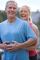 Active senior couple, in sportswear, standing on driveway, woman embracing man wearing blue t-shirt, smiling, portrait